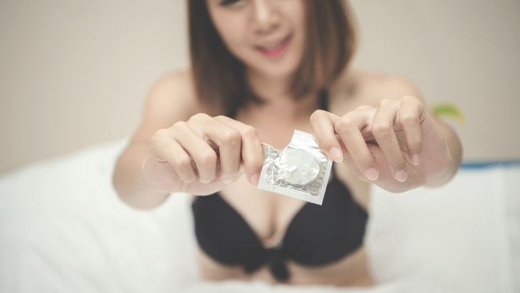 A woman in bed opening a condom