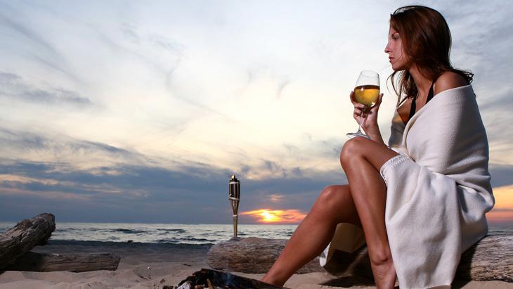 Woman drinking wine on a beach