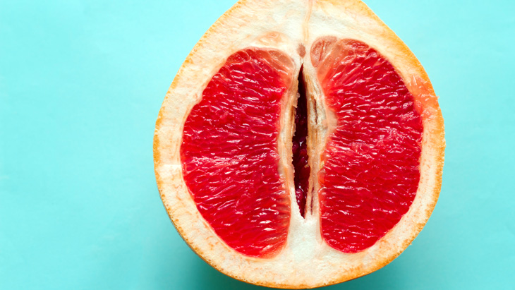 a cut red grapefruit symbolizing a vagina