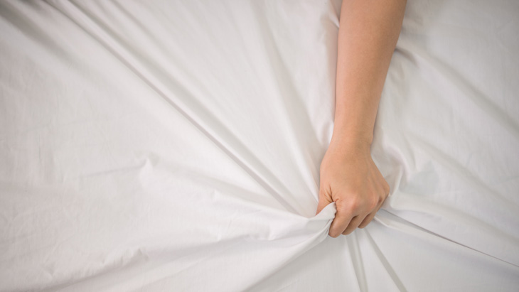 A woman's hand gripping the sheets in pleasure